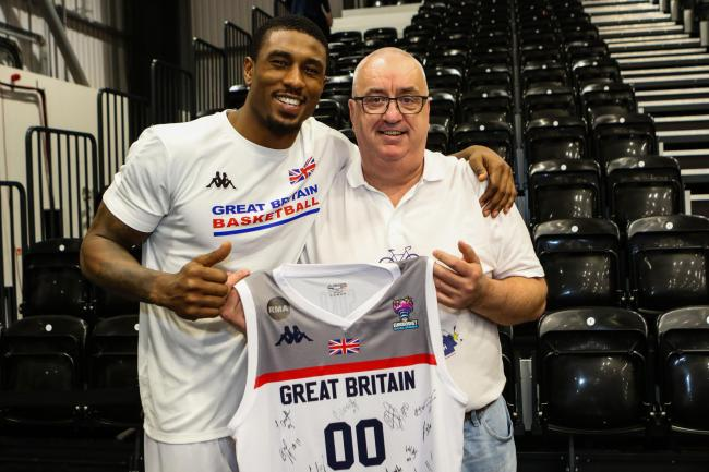 Former Love Island contestant and GB basketball star Ovie Soko presents Andrew Cattle with a signed shirt to be auctioned off for charity