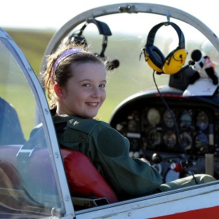 Nine-year-old Ellie Carter uses her toy panda to conduct experiments in aeronautics while instructor Martin Kettle flies over Wiltshire