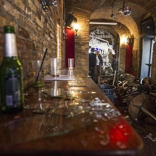 Broken glass, and overturned tables and stools inside The Drunken Ship pub in Rome (AP)