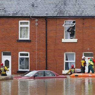 A man looks out of a window as a crew from the RNLI and paramedics pass a submerged car in St Asaph, Denbighshire