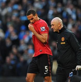 Manchester United's Rio Ferdinand receives treatment to a cut on his head after being struck by an object thrown from the crowd