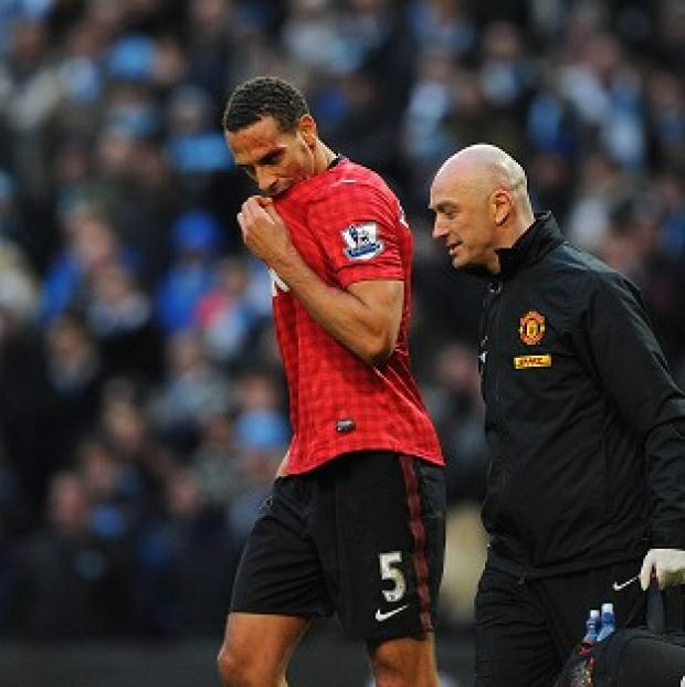 Manchester United's Rio Ferdinand receives treatment to a cut on his head after being struck by a coin thrown from the crowd