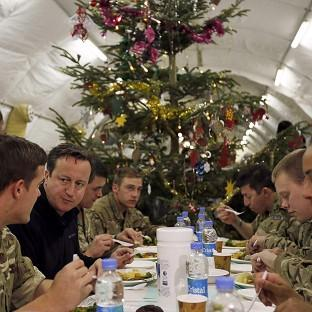 Prime Minister David Cameron eating dinner with British soldiers during a visit to Forward Operating Base Price in Helmand Province, Afghanistan