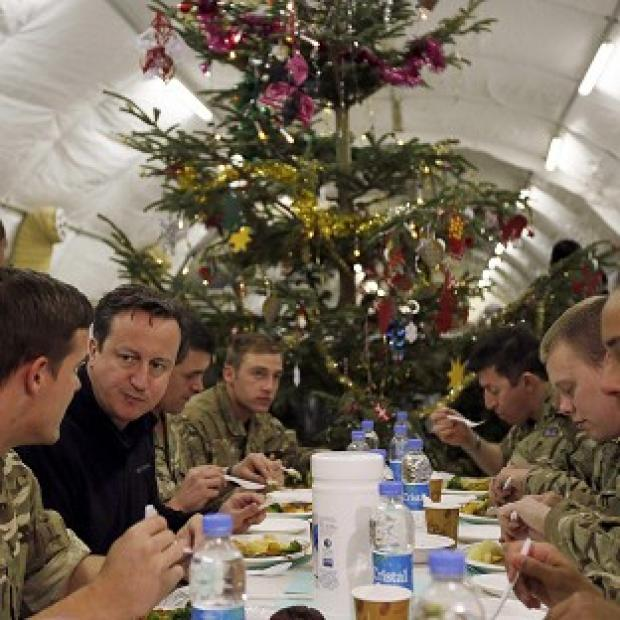 Andover Advertiser: Prime Minister David Cameron eating dinner with British soldiers during a visit to Forward Operating Base Price in Helmand Province, Afghanistan