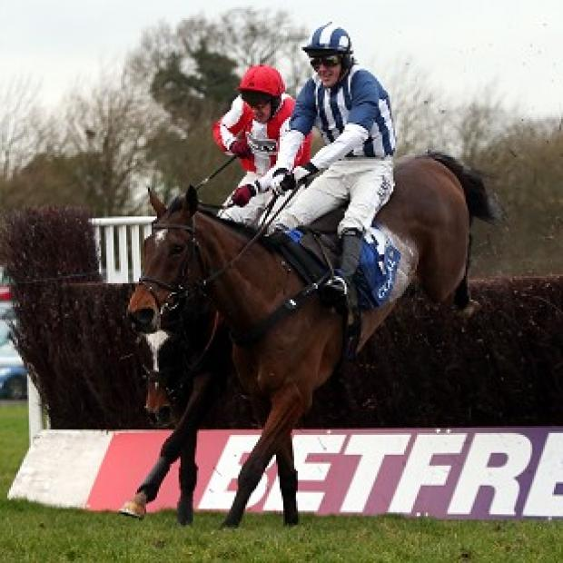 Monbeg Dude, red silks, jumps the last on his way to victory in the Welsh Grand National