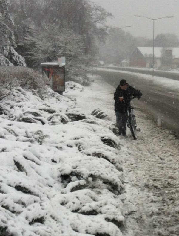 Someone pushing a bike through snow in Ringwood.