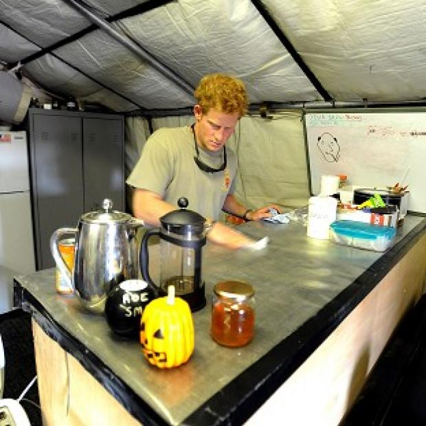 Prince Harry cleaning the kitchen work-top during his 12 hour VHR (very high ready-ness) shift, at the British controlled flight-line in Camp Bastion