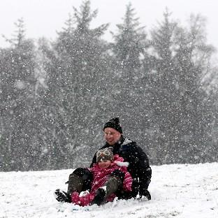 Andover Advertiser: Davie Booth and three year-old daughter Freya sledging in Doune, central Scotland, as snow falls.