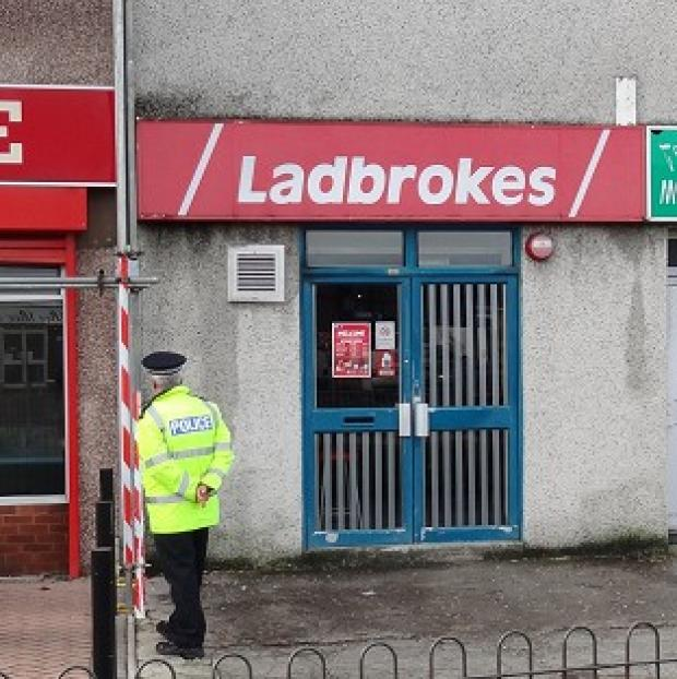 Police at the scene of an attempted armed robbery at Ladbrokes in Plymouth where a masked armed robber collapsed and died