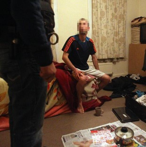 Border Agency Officials in east London search the room of a man suspected of being smuggled into the country