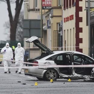 Forensic police officers at the scene of a car crash in which a policewoman was killed on the Limavady Road, Londonderry