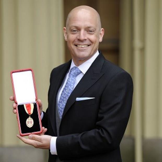 Sir Dave Brailsford poses outside Buckingham Palace with his knighthood
