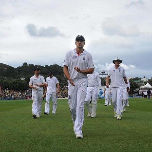 Alastair Cook, centre, leads England off as the rain falls in Wellington