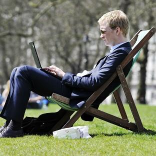 An office worker makes the most of the warm spring weather in Green Park, central London