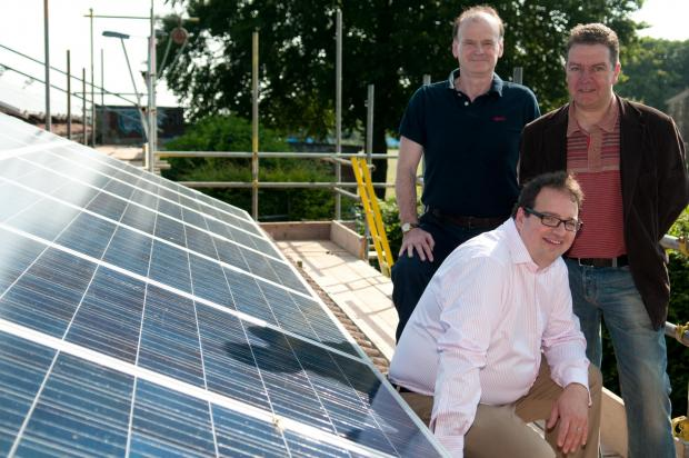 Basingstoke Energy Services Co-op's Martin Heath and Andy Molloy, standing, with Basingstoke and Deane Borough Council's cabinet member for the environment and climate change Cllr Robert Donnell, next to the Whiteditch solar power system