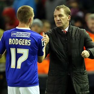 Liverpool manager Brendan Rodgers, right, embraces his son Anton, left, at full time at Anfield