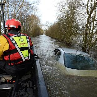 Andover Advertiser: Members of the Avon and Somerset Police Underwater Search Unit inspect a submerged car near Muchelney in Somerset