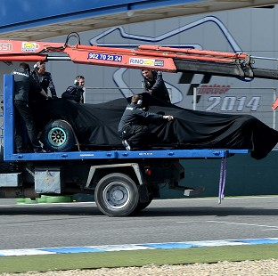 Lewis Hamilton's Mercedes is removed from the track after a crash during testing in Jerez