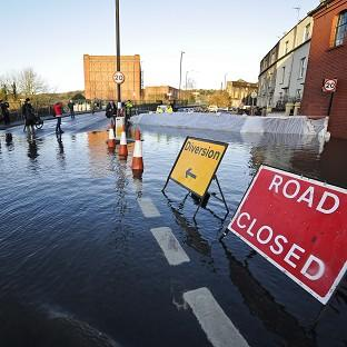 Andover Advertiser: Defence barriers are put in place as the river Avon in Bristol floods surrounding roads
