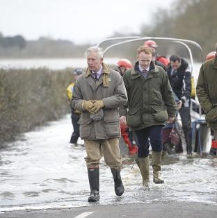Andover Advertiser: The Prince of Wales steps from a boat after travelling to the community of Muchelney and meeting with a local farming family at Thorney Moor Farm, to see the damage caused by floods