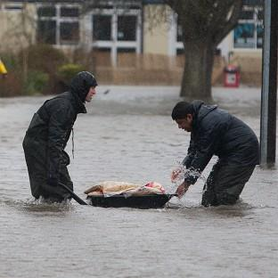 Andover Advertiser: Residents struggle through floodwater in Egham, Surrey.