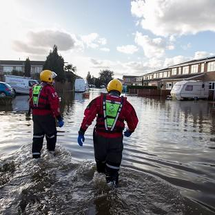 Andover Advertiser: Members of the Surrey Fire and Rescue Service work at a flood-hit housing estate in Staines-upon-Thames
