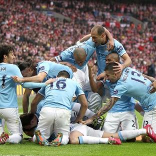 Samir Nasri is mobbed by his team-mates after netting City's second goal