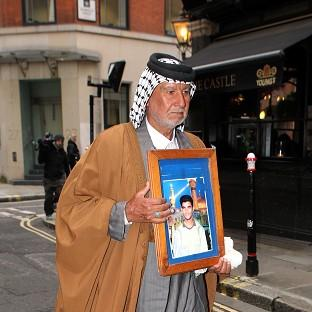Andover Advertiser: Mizal Karim Al-Sweady, the father of Hamid Al-Sweady carries a photo of his son after leaving the inquiry into his death.