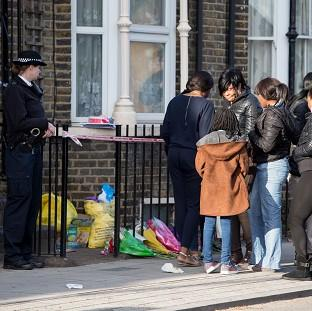 Andover Advertiser: A police officer watches as a group of people gather at the scene in Hackney where Shereka Fab-Ann Marsh, 15, died after a shooting