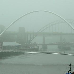 Andover Advertiser: People walk through fog to cross the Tyne Bridge in Newcastle upon Tyne.
