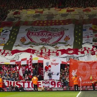 Andover Advertiser: Liverpool supporters hold banners prior to a minute's silence at their match on Sunday