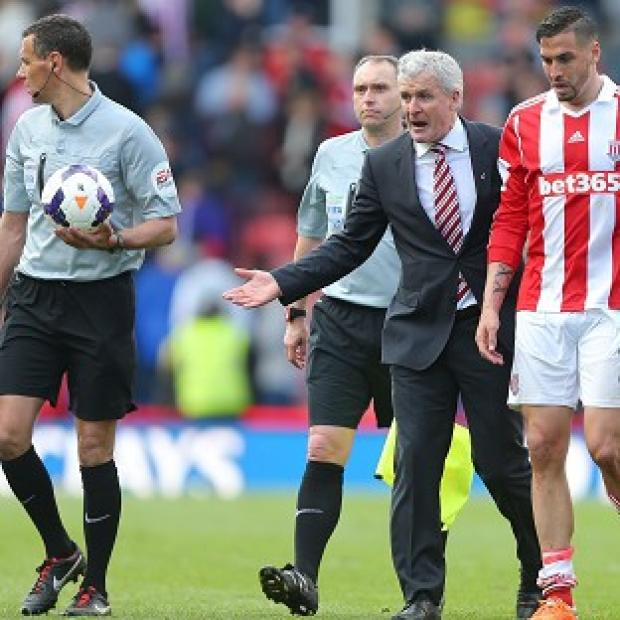 Andover Advertiser: Mark Hughes, centre, was highly critical of the decisions made by referee Andre Marriner, left