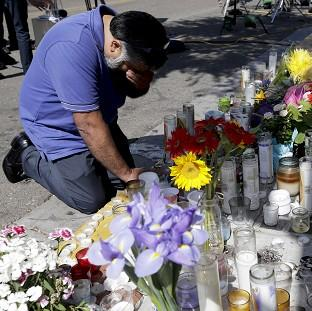 Jose Cardoso pays his respects at a makeshift memorial in front of the IV Deli Mart (AP Photo/Chris Carlson)