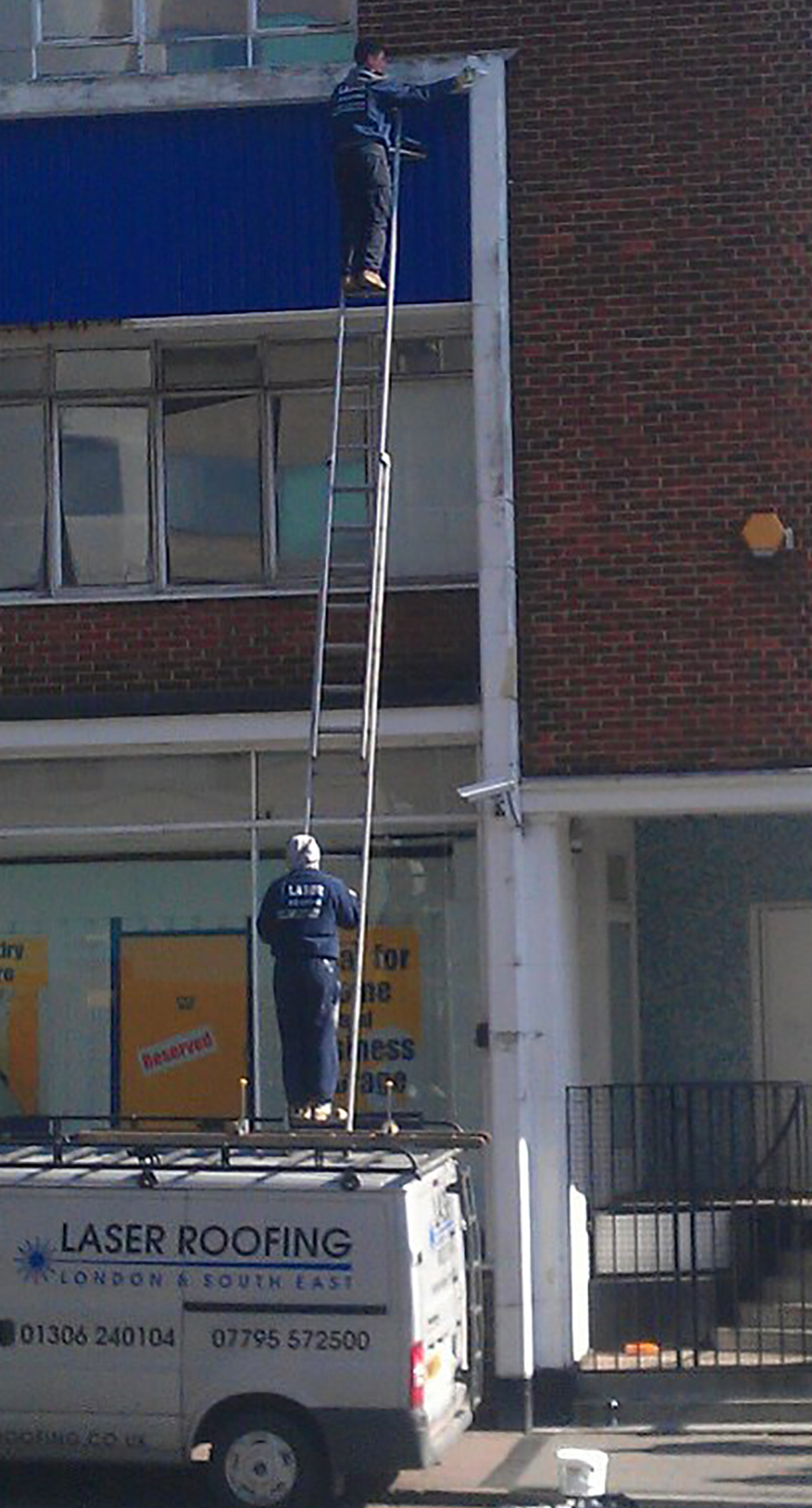Roofer George Nicholls balancing on the ladder on his van whilst working in Southampton
