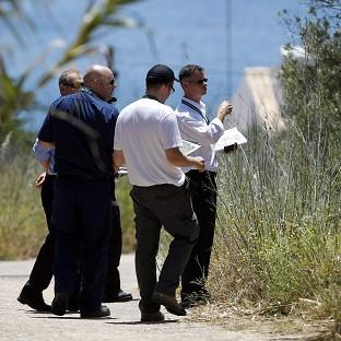 Andover Advertiser: Portuguese and British officials look over the ground inside a cordoned-off area in Praia da Luz (AP)