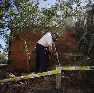 Andover Advertiser: British police officers search the ground using sticks inside a cordoned-off area in Praia da Luz, Portugal