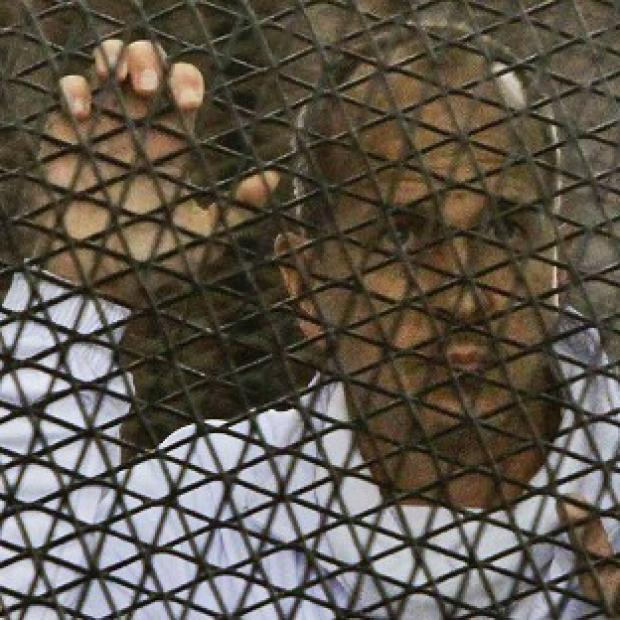 Andover Advertiser: Al Jazeera journalist Peter Greste stands inside the defendants' cage in a Cairo courtroom in March (AP)