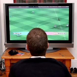 A man plays a computer game on a 50 inch flat screen television.