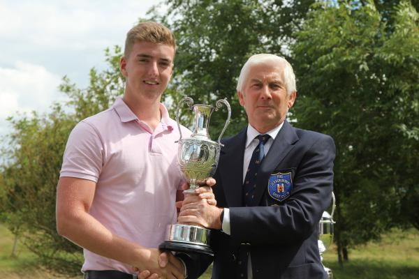 The Hampshire GC champion Will Gilson receives his trophy from club captain Barry Thorne