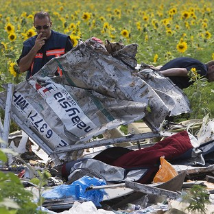 Dutch investigators examine pieces of the crashed Malaysia Airlines Flight 17 in Rassipne, eastern Ukraine (AP)