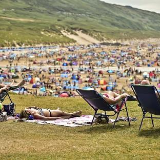 People relax in sunny weather at Woolacombe, North Devon, as the hot w