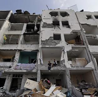 Palestinians inspect damaged buildings in a residential distr