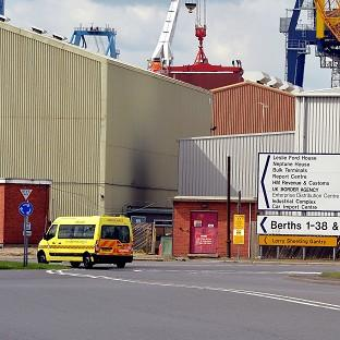 An ambulance van drives into Tilbury Docks in Essex, where a shipping container was found with immigrants inside