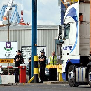 Police officers stand by the main entrance to Tilbury Docks in Essex, where a group of immigrants was found in a shipping container