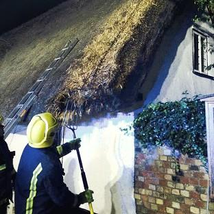 Firefighters inspect a thatched roof following four house fires near Cambridgeshire (Cambridgeshire Fire and Rescue Service/PA)