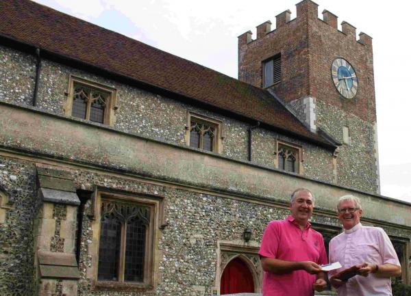 Phil Withington-Smith presents Reverend Phil Collins with a roof tile and £500 cheque