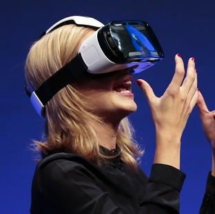 TV presenter Rachel Riley shows a virtual-reality headset called Gear VR, from Samsung, in Berlin. (AP)