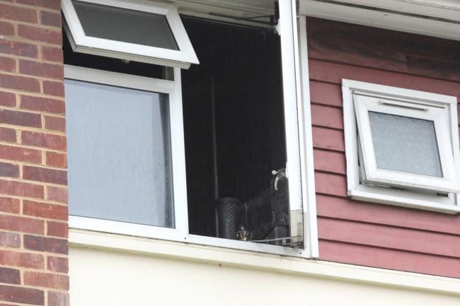 An open window at the property shows some of the damage inside. Photo: Marcus Leon