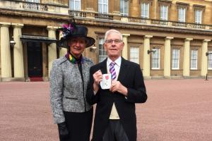 Bruce Parker pictured with his medal and wife Suzanne at Buckingham Palace