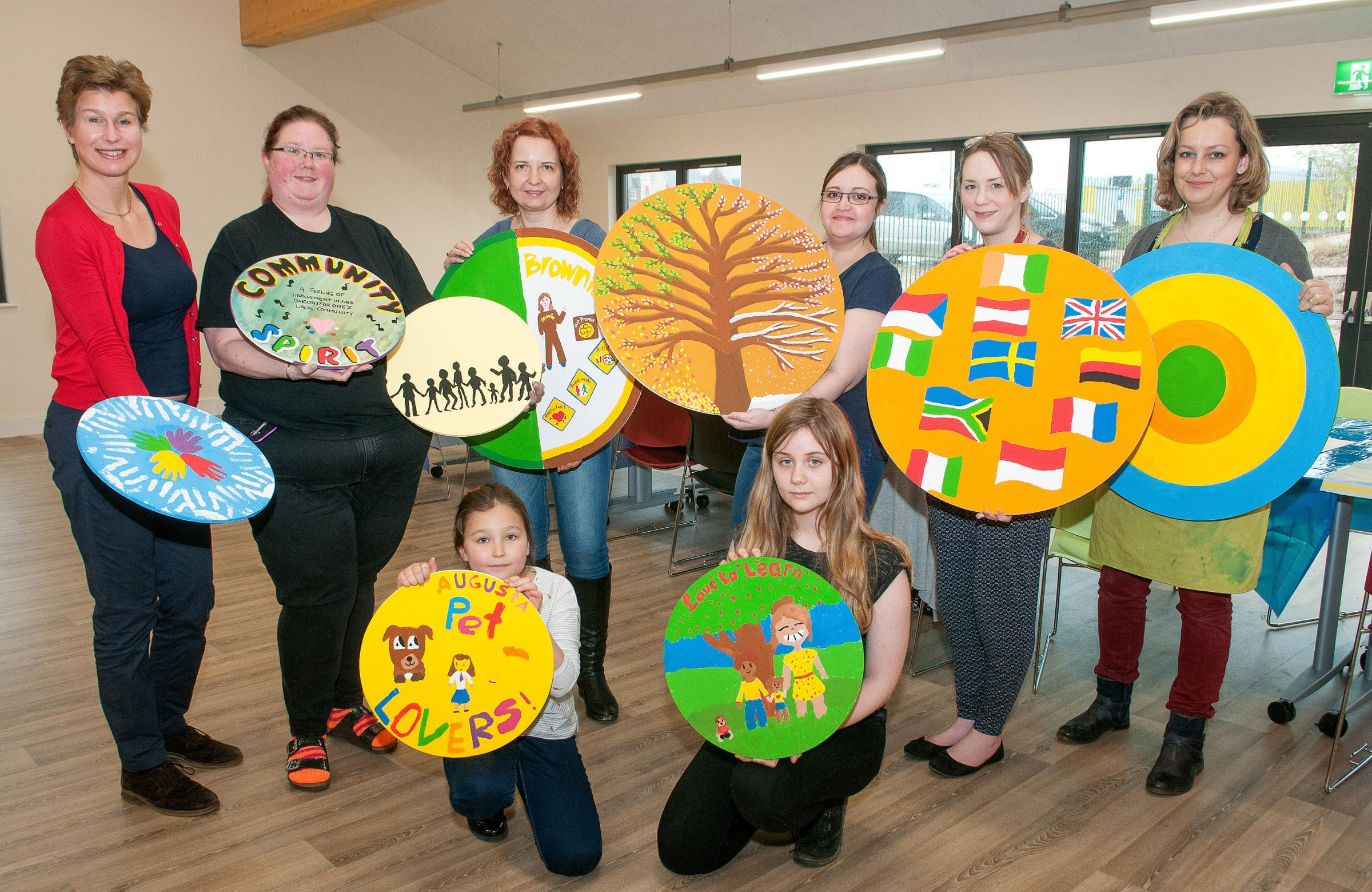 Sally Arscott of Andover YMCA (back left) with with volunteers and their disc designs being painted to make the building a brighter place. Image, Andy Brooks